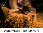 Leather Cowboy Hat on the Small Pile of Hay in the Old Barn. Western Wear and Wild West Concept. - stock photo