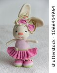 Small photo of Beautiful soft bunny toy with pink dress with ruched dolly skirt and little booties and big bow on head for baby girl handmade with crochet technique from wool and cotton yarn on fluffy white blanket