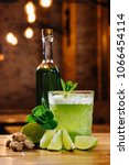 Small photo of close-up view of green van gogh cocktail in glass with bottle of absinthe on wooden table