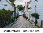 Small photo of Cobblestone street in the old town of Stavanger, Noway. Traditional white wooden houses with red roofs