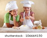 Kids with chef hats preparing a cake or pizza dough - breaking the eggs in the flour heap - stock photo