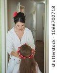 mother put on red flower diadem ... | Shutterstock . vector #1066702718