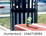 Small photo of humanized figure made of AA battery holds in hands poster with the theta symbol of the earth day. Holiday concept. Copy space for text.