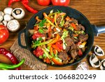 fried meat with vegetables in a ... | Shutterstock . vector #1066820249
