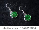 green resin earrings on a dark... | Shutterstock . vector #1066895384