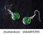 green resin earrings on a dark... | Shutterstock . vector #1066895390