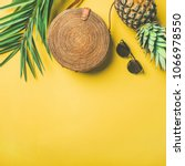 Small photo of Colorful summer female fashion outfit flat-lay. Straw hat, bamboo bag, sunglasses, palm branches, pineapple over yellow background, top view, copy space, square crop. Summer fashion, holiday concept