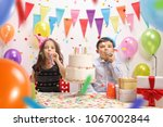 Small photo of Little girl and a little boy with party horns and a cake celebrating a birthday