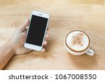 hand holding mobile phone while ... | Shutterstock . vector #1067008550