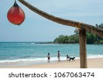 Small photo of Tangalle, Sri Lanka - March 2018: Children and dog play along the shoreline of beautiful tropical beach, with orange netted buoy on post in foreground