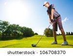 Male Golf Player Teeing Off...