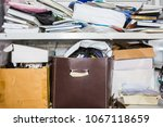 Small photo of clutter concept - lots of books, papers, boxes on shelf - chaos, order, mess, unorganized