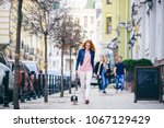 Stock photo a young redhaired caucasian woman walking along european street with small chihuahua breed dog of 1067129429