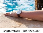 a woman lounging by a swimming... | Shutterstock . vector #1067225630