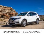 Small photo of Red Rock Canyon State Park, California / USA - 05 16 2017: White Nissan Rogue on gravel road in front of sandstone formation in desert wilderness area