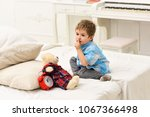 Small photo of Child in bedroom with silence gesture. Kid put plush bear near pillows and alarm clock, luxury interior background. Time to sleep concept. Boy with calm face puts favourite toy on bed, time to sleep.