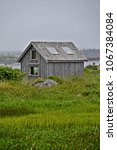 Small photo of Peggy's Cove, Nova Scotia/Canada- July 7, 2016: A vertical image of a weathered batten board cottage by the sea in the Canadian maritimes.