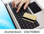 Close up of laptop computer with a credit card and a hand - payment concept - stock photo