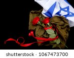 Small photo of Israeli flag and uniforms with red flowers for the memorial day on black background