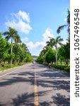 Small photo of Clean and straight asphalt road with green palm trees along the road. Man riding motorbike and car on road in distance. City of Sanya, China.