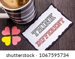 Small photo of Handwriting text Think Different. Concept meaning Rethink Change on vision Acquire New Ideas Innovate written on Sticky Note Paper on the wooden background Coffee Cup and Heart next to it.