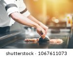 hand of man take cooking of... | Shutterstock . vector #1067611073