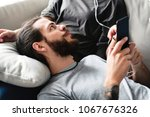 interracial couple on a couch... | Shutterstock . vector #1067676326