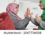 muslim mother and daughter... | Shutterstock . vector #1067736038