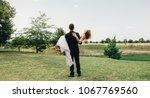bridegroom carrying his bride... | Shutterstock . vector #1067769560