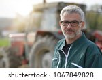 farmer standing by tractor... | Shutterstock . vector #1067849828