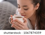 beautiful young woman with cup... | Shutterstock . vector #1067874359