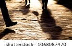 Blurry legs  silhouettes and shadows of people walking on city patterned square in sunset - stock photo