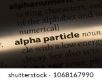 Small photo of alpha particle word in a dictionary. alpha particle concept.