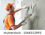 plasterer putting plaster on... | Shutterstock . vector #1068312893