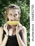 Close-up outdoor portrait of young beauty woman eating corn-cob - stock photo