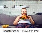 fat funny man in pajamas eating ...   Shutterstock . vector #1068544190