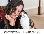 Stock photo young woman bonding with calico cat bumping rubbing bunting heads friends friendship companion pet 1068560120