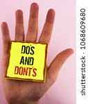 Small photo of Text sign showing Do'S And Don'Ts. Conceptual photo What can be done and what cannot be knowing right wrong written Yellow Sticky Note Paper placed the Hand the plain background.