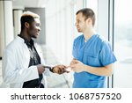 two doctors talking as they... | Shutterstock . vector #1068757520