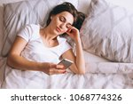 Woman With Phone In Bed