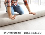 man rolling out new carpet... | Shutterstock . vector #1068783110