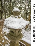 Stock photo fresh snow covers an ancient stone lantern at the entrance to a shinto shrine in a winter forest in 1068812468