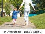 happy girl kid walking with her ... | Shutterstock . vector #1068843860