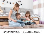 nanny reading book to little... | Shutterstock . vector #1068885533