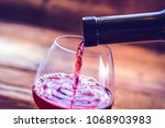 red wine is poured into a glass.... | Shutterstock . vector #1068903983