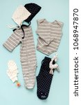 Small photo of set of children's clothes for a newborn boy and girl on a blue background: a body to choose from, a cap to choose from, trousers and mittens for protection. Collection spring-summer