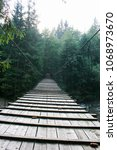 Small photo of Suspended wooden bridge across the mountain river.