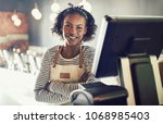 smiling young african waitress... | Shutterstock . vector #1068985403