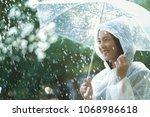 rainy day asian woman wearing a ...   Shutterstock . vector #1068986618