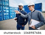 two engineers wearing hardhats... | Shutterstock . vector #1068987686